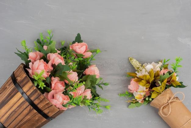 Twee mooie boeketten bloemen op grijze ondergrond.