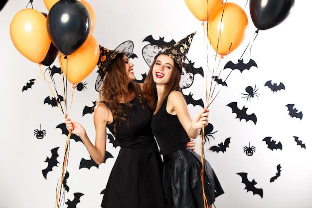 Twee mooie brunette meisjes gekleed in zwarte jurken en heksenhoeden houden zwarte en oranje ballonnen vast. halloween.
