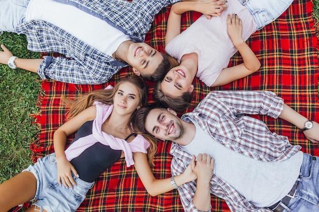 Twee mooie dames met hun knappe jongens zitten in een park op een deken en kijken naar de camera