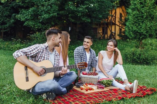 Twee mooie dames met twee jongens zitten in een park op een dekentapijt met gitaar