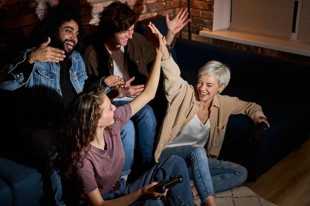 Twee mooie dames vieren overwinning op gameconsole, winnend concept. vrouwen lachen, geven elkaar high five