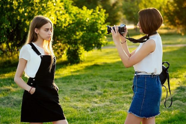 Twee mooie dames vrienden in het park fotograferen op een professionele camera. fotoshoot fotosessie in de stad