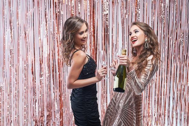 Twee mooie elegante vrouwen die champagne drinken tegen fonkelende decoratie