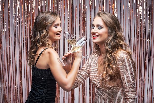 Twee mooie elegante vrouwen die in avondjurken champagne drinken.