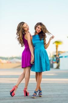 Twee mooie elegante vrouwen in cocktailjurken 's avonds wandelen langs de promenade