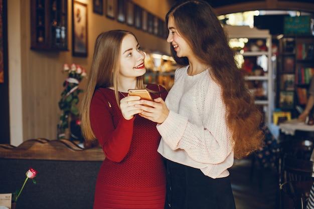 Twee mooie en elegante vrienden die zich in een koffie bevinden en de telefoon gebruiken