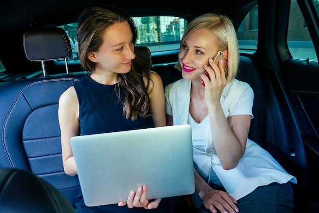 Twee mooie en jonge brunette en blonde zakenvrouwen werken buiten kantoor in auto met laptop in pak jurk rijk en praten aan de telefoon luxe concept