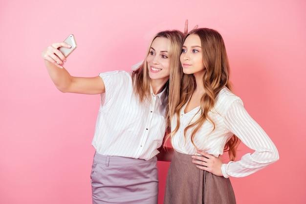 Twee mooie en lachende vrouwelijke personen moeder en dochter nemen foto's selfie aan de telefoon op een roze achtergrond in de studio. concept van liefde en familie.