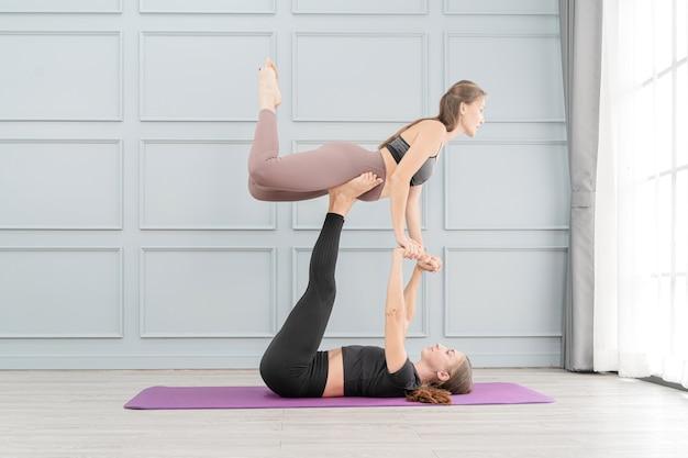 Twee mooie fit vrouwen beoefenen van yoga met geavanceerde houding. jonge vrouwen met een magere donkere suite die lichaamsbalans en harmonie samenbrengen.