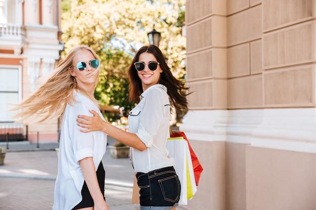 Twee mooie fotomodellen samen poseren buiten met boodschappentassen