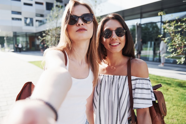 Twee mooie gelukkig jonge student meisje met rugzak in de buurt van de campus van de universiteit. onderwijs en recreatie concept