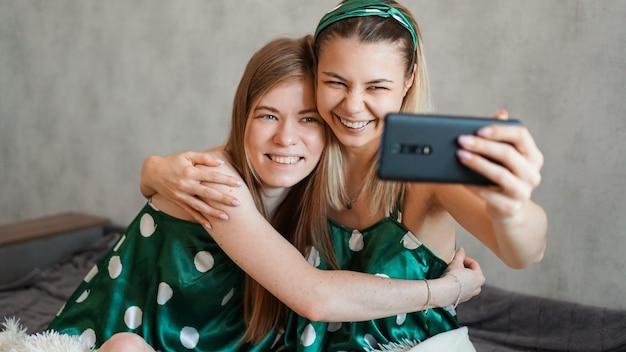 Twee mooie gelukkige vriendinnen knuffelen en nemen van selfies met smartphone op pyjamafeestje