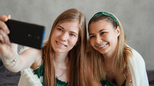 Twee mooie gelukkige vriendinnen selfie met smartphone op pyjamapartij