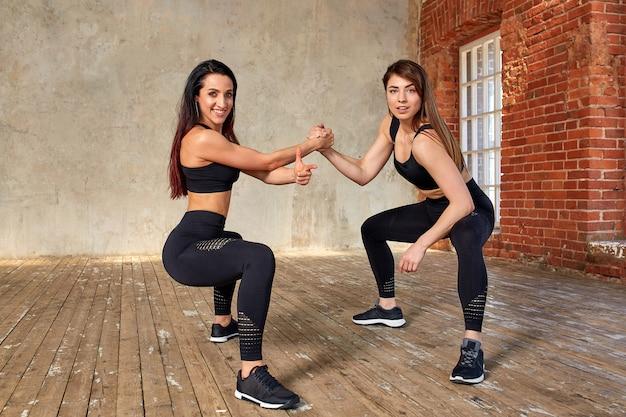 Twee mooie glimlachen, fitness meisjes doen oefeningen in de fitnessruimte geven vijf. concept sport, teamwork.