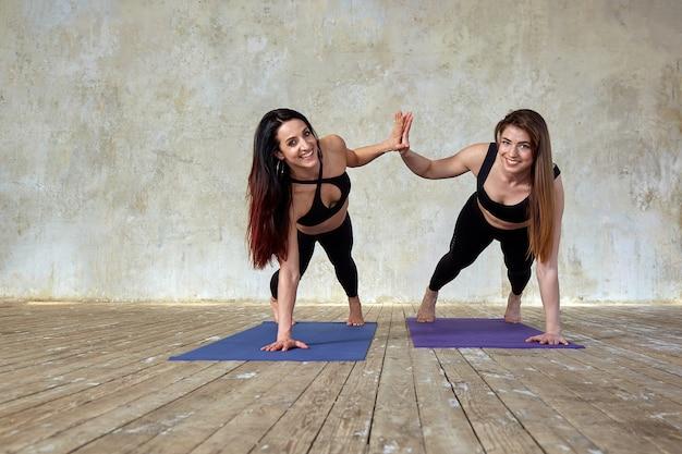 Twee mooie glimlachende, fitnessmeisjes die oefeningen in de fitnessruimte doen geven vijf.