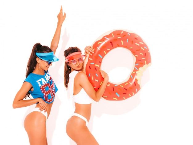 Twee mooie glimlachende sexy vrouwen in witte de zomeronderbroek en onderwerp. meisjes in zonnebril, transparante vizierkap. positieve modellen hebben plezier met opblaasmatras met donut lilo. geïsoleerd