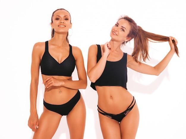 Twee mooie glimlachende sexy vrouwen in zwarte lingerie