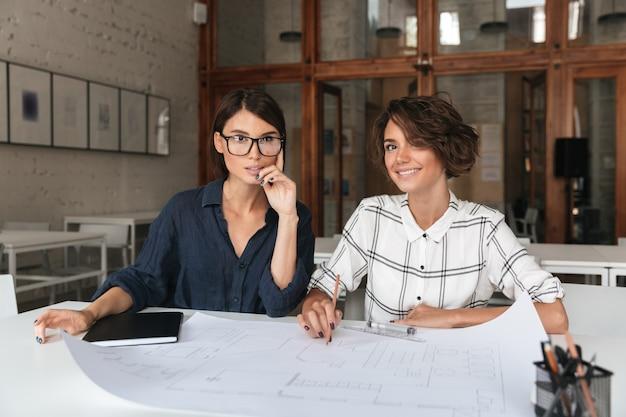 Twee mooie glimlachende vrouwen zitten bij de tafel