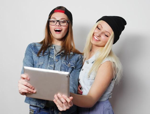 Twee mooie hipstermeisjes die een zelfportret met een tablet, over witte niet geïsoleerde achtergrond nemen