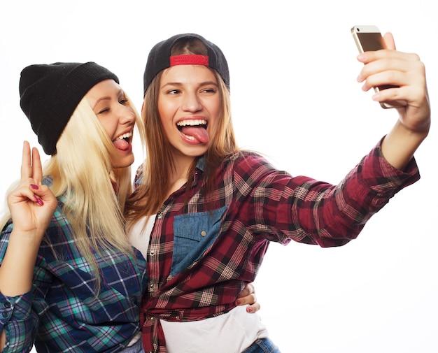 Twee mooie hipstermeisjes die selfie nemen. geïsoleerd op een witte achtergrond.