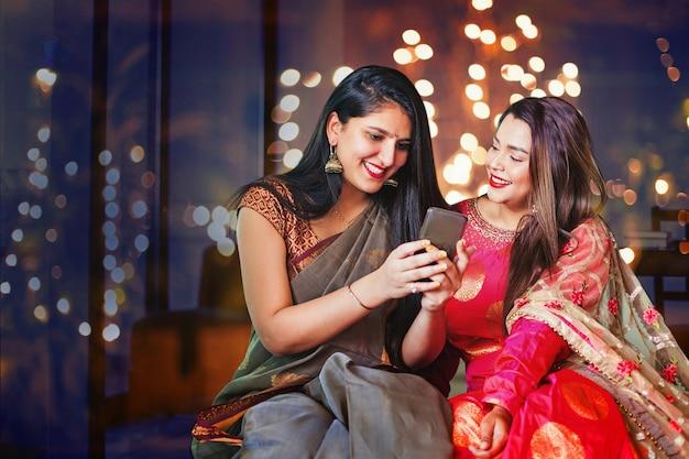 Twee mooie indiase vrouwen in etnische kleding doen diwali online winkelen met behulp van mobiele telefoon