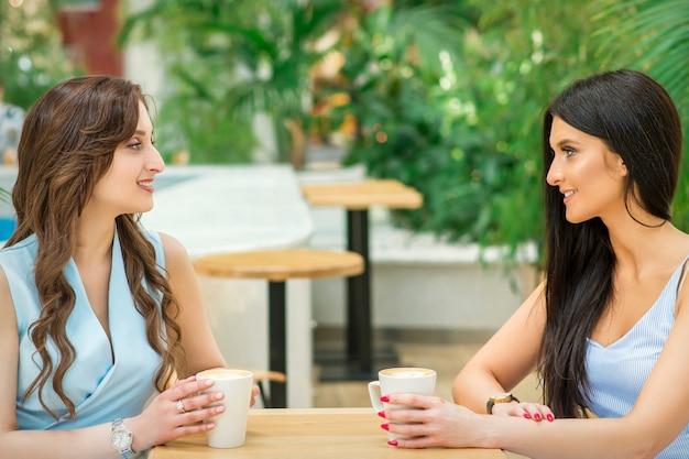 Twee mooie jonge blanke vrouwen drinken koffie zittend aan tafel in café buiten