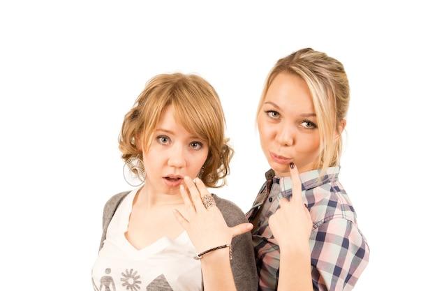 Twee mooie jonge blonde meisjes die geamuseerd scepticisme en verrassing uiten