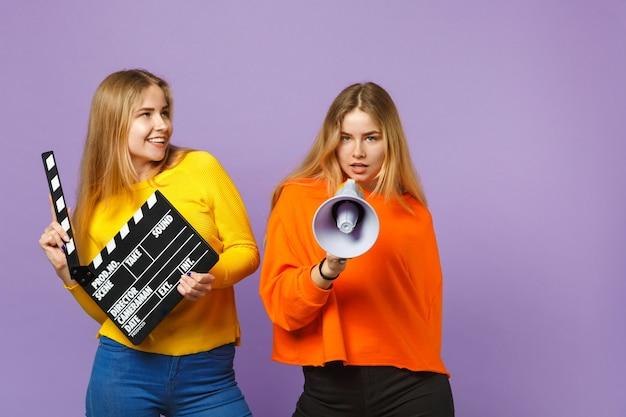 Twee mooie jonge blonde tweeling zussen meisjes houden klassieke zwarte film filmklapper, schreeuwen op megafoon geïsoleerd op violet blauwe muur. mensen familie levensstijl concept. .