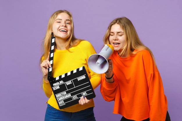 Twee mooie jonge blonde tweelingzusters meisjes houden klassieke zwarte film filmklapper, schreeuwen op megafoon geïsoleerd op violet blauwe muur. mensen familie levensstijl concept.