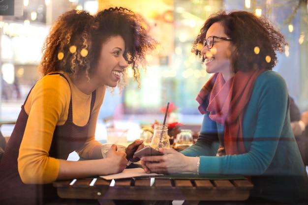 Twee mooie jonge dames zitten in een bar, chatten en lachen