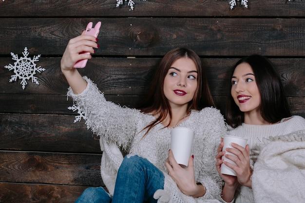 Twee mooie jonge grappige vrouwenvrienden die en pret glimlachen hebben, maken salfie