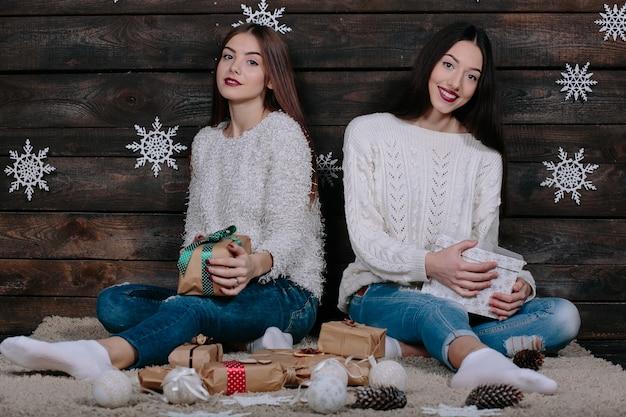 Twee mooie jonge grappige vrouwenvrienden glimlachen en geven elkaar geschenken
