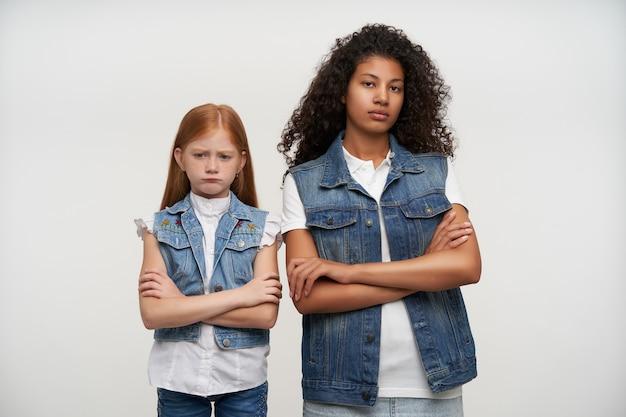 Twee mooie jonge langharige teleurgestelde dames die handen op hun borst vouwen die zich op wit in vrijetijdskleding bevinden, die over iets van streek zijn