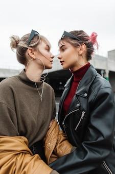 Twee mooie jonge lesbische meisjes in modieuze kleding met leren jas op straat