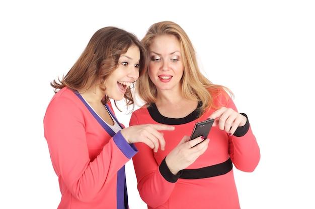 Twee mooie jonge meisjes die goederen kiezen in een internetwinkel