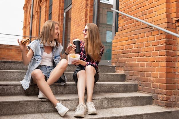 Twee mooie jonge meisjes eten fastfood op straat, ze hebben lol, praten en voeren elkaar heerlijke dingen.
