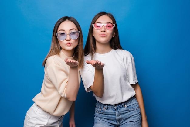 Twee mooie jonge meisjes gekleed in zomerkleren staan ?? en verzenden kus geïsoleerd over blauwe muur