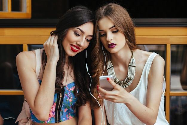 Twee mooie jonge meisjes houden vintage vast