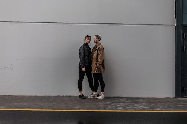 Twee mooie jonge meisjes in een trendy herfstoutfit met een vintage leren jas en zwarte spijkerbroek staan in de buurt van een minimalistische grijze muur op straat