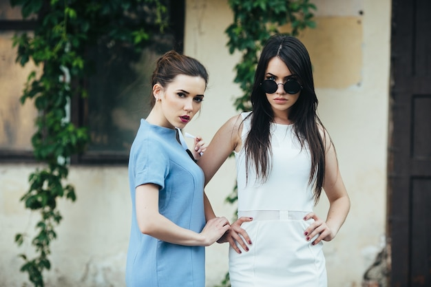 Twee mooie jonge meisjes in jurken poseren voor het huis