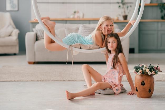 Twee mooie jonge meisjes in prachtige jurken rijden swing en poseren.