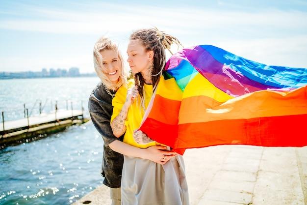 Twee mooie jonge meisjes knuffelen op het strand met een regenboogvlag.