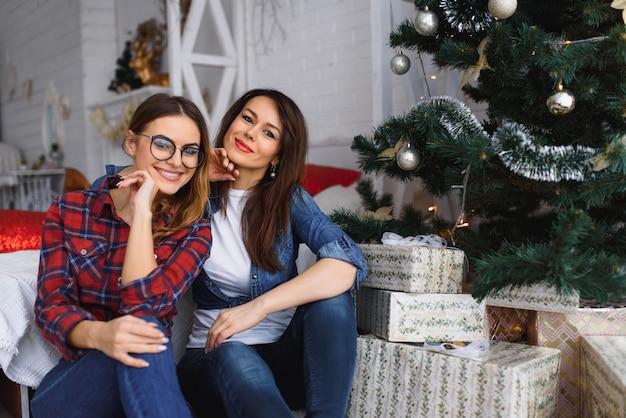 Twee mooie jonge meisjes of vrouwen zitten dichtbij een nieuwjaar of een kerstboom.