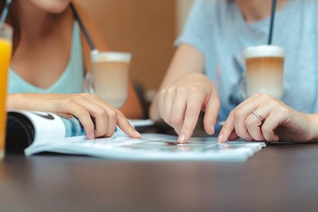 Twee mooie jonge meisjes zitten bij de tafel in café