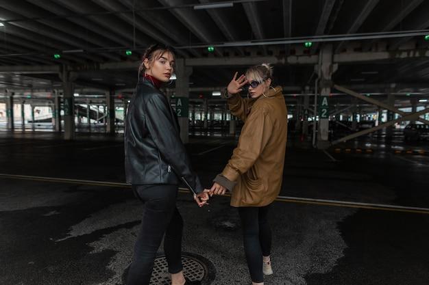 Twee mooie jonge meisjesmodellen in modieuze, stijlvolle leer- en jeanskleding lopen op de parkeerplaats in de stad