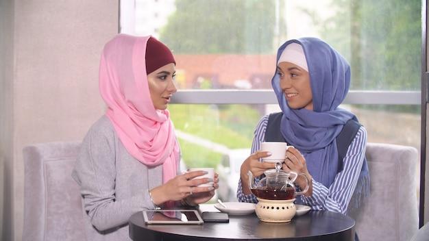 Twee mooie jonge moslima's in cafe communiceren.