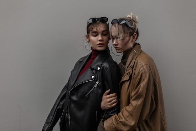 Twee mooie jonge stijlvolle vrouwenmodellen in modezonnebrillen met vintage leren jas in de buurt van grijze muur in de stad