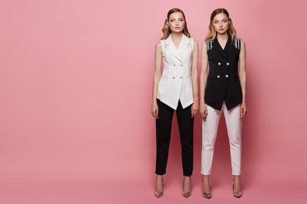 Twee mooie jonge tweeling vrouwen met slanke perfecte lichamen in zwart-wit pakken, met make-up en emotieloze gezichten, poseren op volle lengte op de roze achtergrond, geïsoleerd