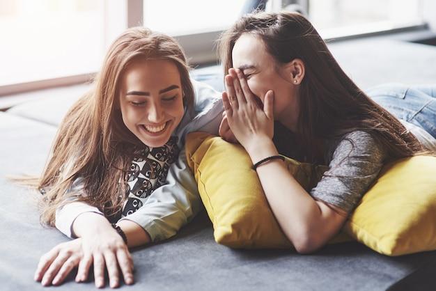 Twee mooie jonge tweelingzussen die tijd samen met kussens doorbrengen. broers en zussen plezier thuis concept