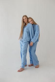 Twee mooie jonge tweelingzussen met lang blond haar poseren